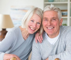 elderly couple smiling with dental implants in State College