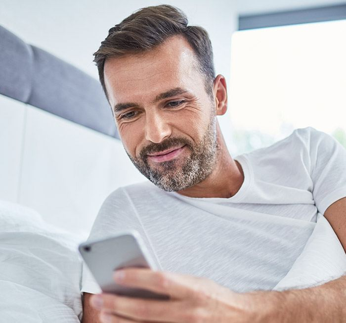 Man in bed checking cell phone