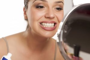 young woman looking at her teeth in a mirror