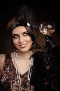 woman in 1920s smiling with champagne