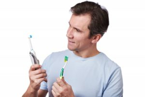 A man comparing electric and manual toothbrushes.
